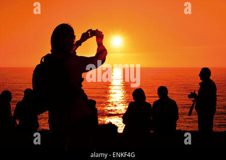 Portugal, Algarve: Tourists taking snapshot of sunset at Cape Saint Vincent in Sagres - Stock Photo