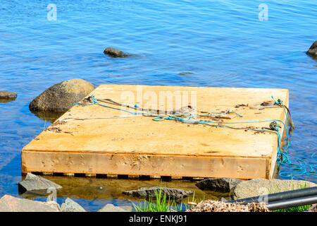 Wooden floating work platform by the shore close to stones. Blue water around and some ropes on the platform. - Stock Photo