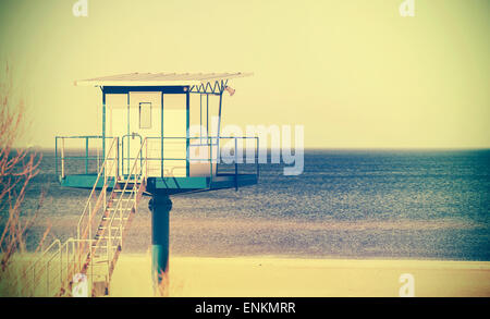 Retro cross process style filtered picture of a lifeguard tower on a beach. - Stock Photo