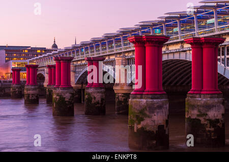 Blackfriars bridge with columns of purple pillars next to it - Stock Photo