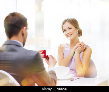 excited young woman looking at boyfriend with ring - Stock Photo
