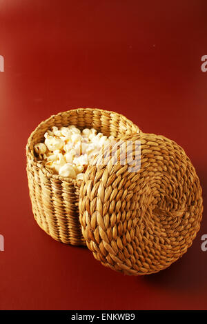 popcorn in basket isolated over red background - Stock Photo