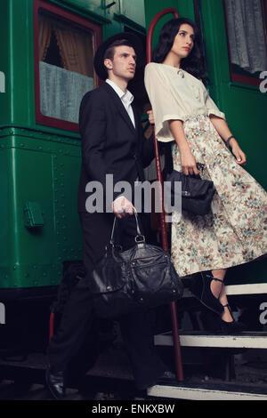 Fashionable couple posing on vintage train car - Stock Photo