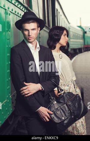 retro fashionable man at vintage railway station - Stock Photo