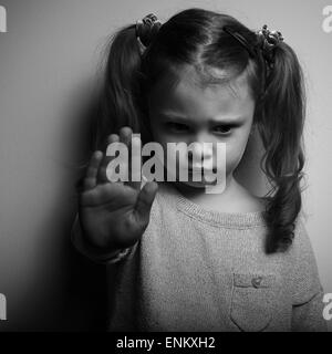 Kid girl showing hand signaling to stop violence and pain and looking down with sad face. Black and white portrait - Stock Photo