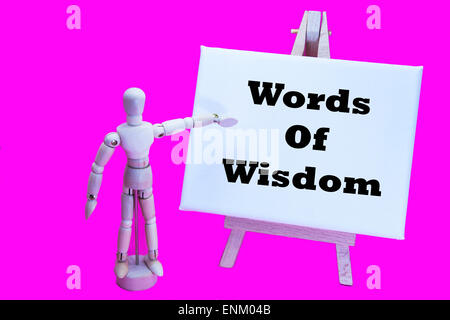 Wooden man with white board pointing at words 'words of wisdom' useful advice help advising helping talking  elder - Stock Photo