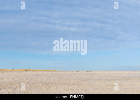 Beach with many foot steps, beach grass, clouds, blue sky - Stock Photo