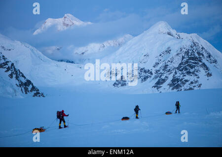 A team of three climbers on their way to base camp after reaching the summit of Mount McKinley, also known as Denali - Stock Photo