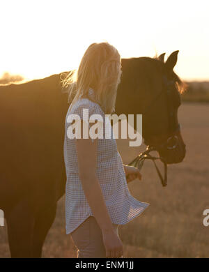 A young woman leading an Arabian horse - Stock Photo
