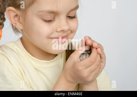 Six year old girl smiling holding pens in the hamster - Stock Photo