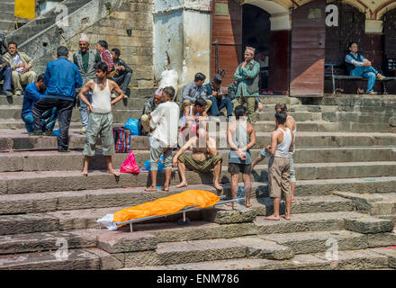 Pashupatinath Temple in Kathmandu. A family is waiting for a cremation ceremony next to a dead body. - Stock Photo