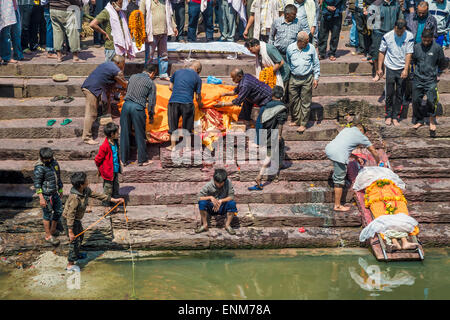 Pashupatinath Temple in Kathmandu. A dead body is washed by a relative - Stock Photo