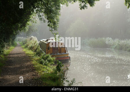 Tow path and a narrow boat moored on the banks of the Kennet & Avon Canal tree-lined on a bright misty late summer - Stock Photo