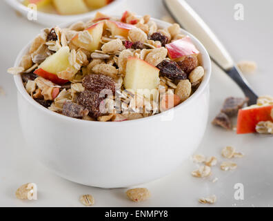 Muesli and fruits for breakfast in a white bowl. Selective focus - Stock Photo