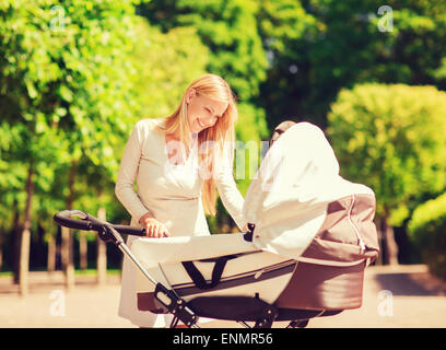 happy mother with stroller in park - Stock Photo