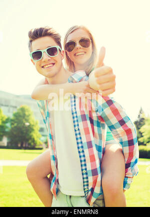 smiling couple having fun and showing thumbs up - Stock Photo