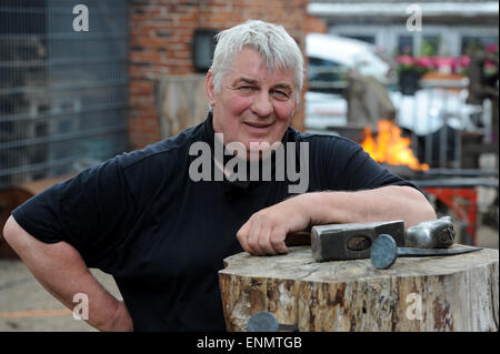 Friesoythe, Germany. 8th May, 2015. Actor Heinz Hoenig works on a nail at the 'Bullermanns Schmiedeatelier' (lit. - Stock Photo
