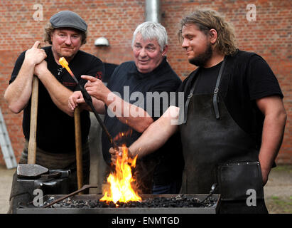 Friesoythe, Germany. 8th May, 2015. Actor Heinz Hoenig and smiths Tom Carstens (l), and Denni Ludwig (r), work on - Stock Photo