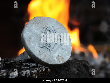 Friesoythe, Germany. 8th May, 2015. A newly forged 'Friedensnagel' ('peace nail') next to the fire in 'Bullermanns - Stock Photo