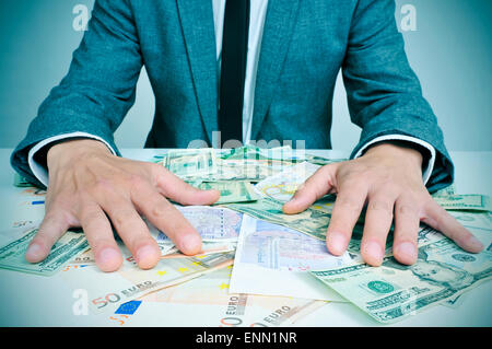 closeup of a young caucasian man in suit sitting at his office desk full of euro and dollar bills trying to hold - Stock Photo