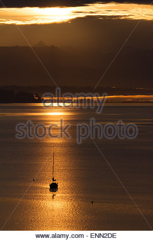 Sunrise morning rays are reflected in Puget Sound as the sun rise over teh Cascade Mountains with a sailboat moored - Stock Photo
