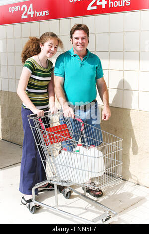 Father and teenage daughter shopping for water in preparation for a drought, hurricane, or other disaster. - Stock Photo