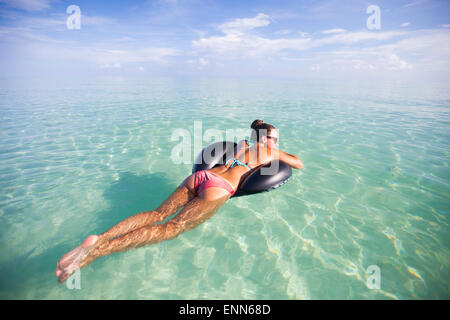 A young woman floats on an inflatable water toy in shallow turquoise water. - Stock Photo