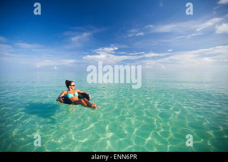 A young woman floats on an inflatable water toy in turquoise water. - Stock Photo