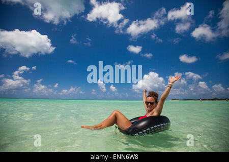 A young woman wearing a bikini floats on an inflatable tube in turquoise water while on vacation in Cayo Coco, Cuba. - Stock Photo