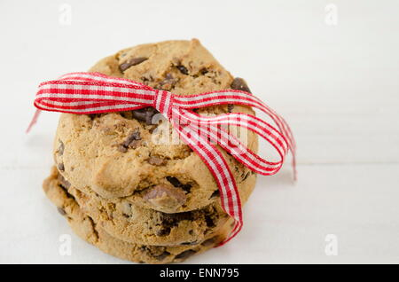 Chocolate chip cookies tied together with a red ribbon on white - Stock Photo
