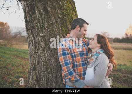 Portrait of a husband and wife smiling at each other. - Stock Photo
