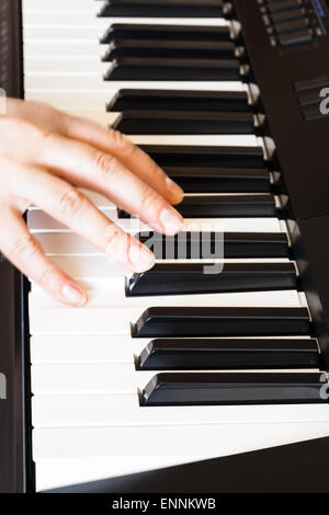 musician playing music on black and white keys of piano close up - Stock Photo