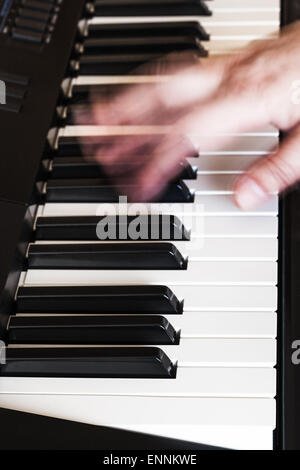 musician playing music on black and white keys of synthesizer close up - Stock Photo