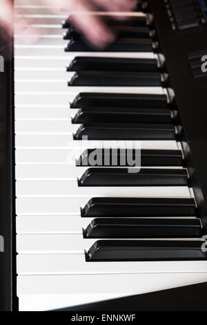 musician playing music on black and white keys of digital piano close up - Stock Photo