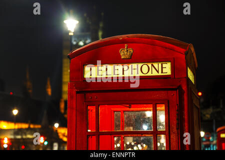Famous red telephone booth in London, UK at night - Stock Photo
