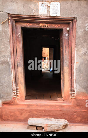 Typical low wooden doorway at entrance to old Newari house in Bhaktapur, Nepal - Stock Photo