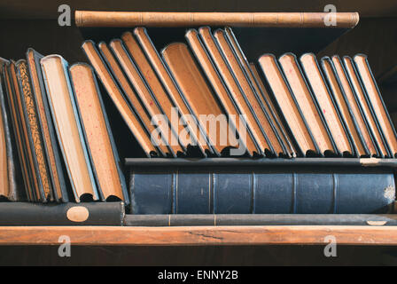 Old books in a vintage library shelves - Stock Photo