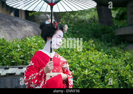 Geisha in traditional clothing and oil-paper umbrella (wagasa) in Kyoto, Japan - Stock Photo
