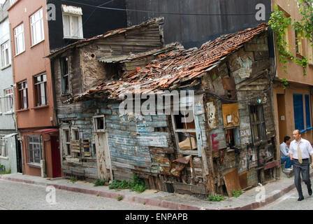 A decrepit shack wedged into the corner of a modern row of buildings in downtown Istanbul, Turkey - Stock Photo