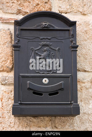 Antique black metal mail box on the old wall - Stock Photo