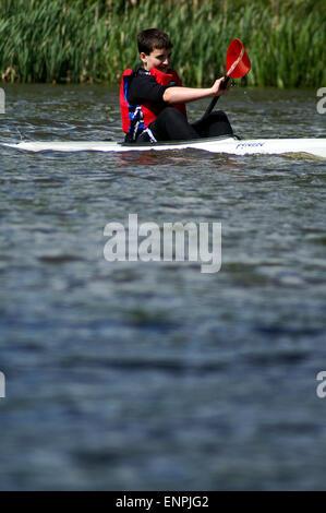 Boy competing in a K1 racing kayak - Stock Photo