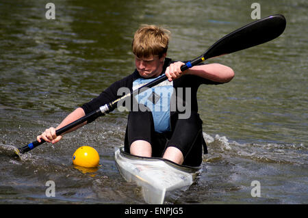 Young man competing in a K1 racing kayak - Stock Photo
