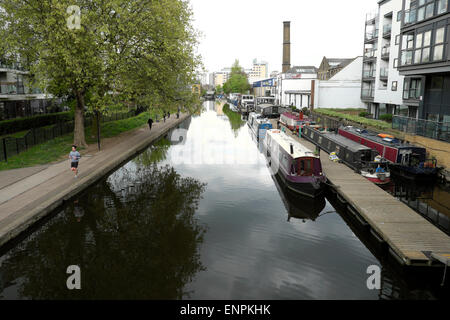 A view towards Sturts Lock of houseboats moored at Regents Canal near Shepherdess Walk with a jogger jogging on - Stock Photo