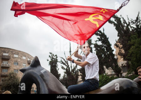 Jerusalem, Israel. 10th May, 2015. A VE-Day march participant is waving the Soviet Union national flag before the - Stock Photo