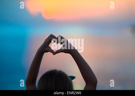 Silhouette of heart made by kids hand at sunset