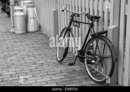 A bicycle leaning against railings, with milk churns in the background, at Bewdley railway station on the Severn - Stock Photo