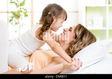 Happy mother and child girl embracing and kissing in bed - Stock Photo