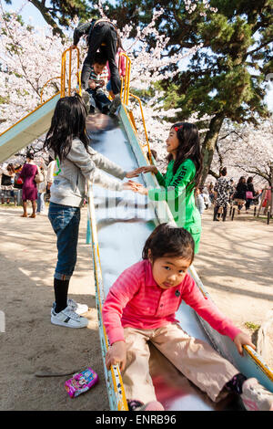 Japan, Nishinomiya, Shukugawa. Young Japanese boy on slide with two girls on either side holding hands in the park - Stock Photo