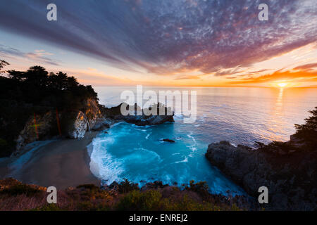 Beautiful sunset of McWay Falls into the Pacific Ocean along the Big Sur Coast of California just north of the Esalen - Stock Photo