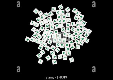 Landscape image of white word game tiles with green lettering on a black background - Stock Photo